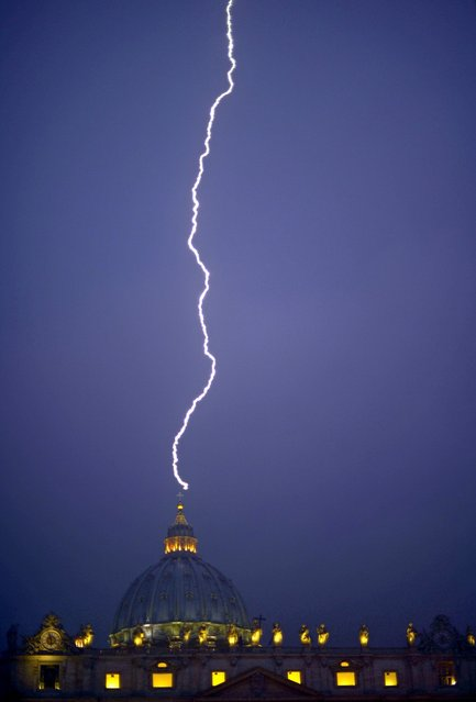A lightning strikes St Peter's dome at the Vatican on February 11, 2013. Pope Benedict XVI announced today he will resign as leader of the world's 1.1 billion Catholics on February 28 because his age prevented him from carrying out his duties – an unprecedented move in the modern history of the Catholic Church. (Photo by Filippo Monteforte/AFP Photo)
