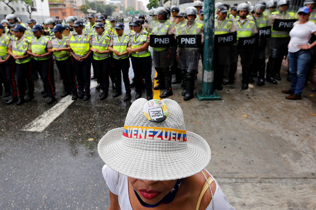 An opposition supporter stands in front of police during a rally to demand a referendum to remove President Nicolas Maduro in Caracas, Venezuela July 27, 2016. (Photo by Carlos Jasso/Reuters)