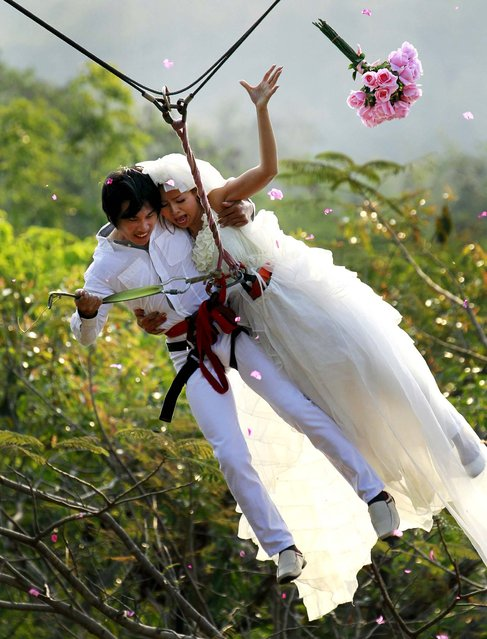 Sopon Tapoatong and his bride Chutuma Tapoatong swing out on a rappelling rope as part of an adventure-themed wedding ceremony in Prachinburi province, Thailand, on the eve of Valentine's Day, on February 13, 2013. (Photo by Wason Wanichakorn/Associated Press)