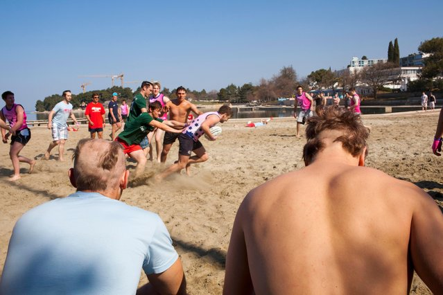 Two British university students with chunks shaved out of their hair, watch rugby being played on the beach at the Zelena Laguna resort near Porec on March 29, 2012. They are on the inaugural ILOVETOUR to the town in Croatia. The tour organizes various sports and themed events and club nights. (Photo by Peter Dench/Getty Images Reportage)