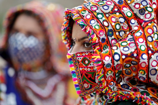A participant in a traditional costume wearing a face mask attends a rehearsal for Garba, a folk dance, ahead of Navratri, a festival during which devotees worship the Hindu goddess Durga and youths dance in traditional costumes, amidst the coronavirus disease (COVID-19) outbreak, in Ahmedabad, India, September 12, 2020. (Photo by Amit Dave/Reuters)