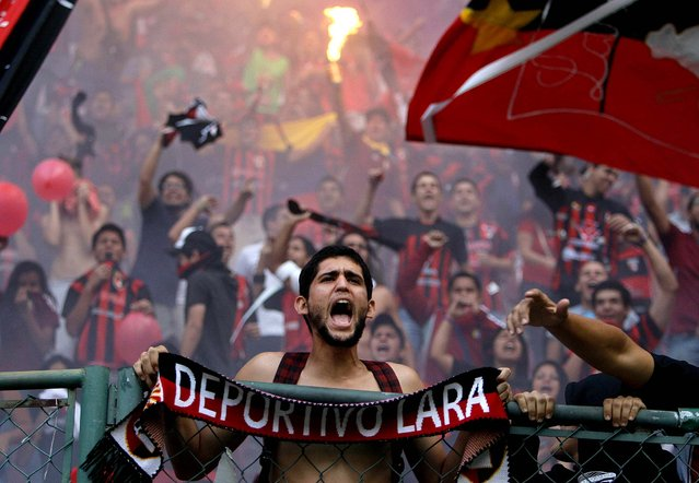 A fan of Venezuela's Deportivo Lara cheers his team during a Copa Libertadores soccer match against Argentina's Newell's in Barquisimeto, Venezuela, February 21, 2013. (Photo by Fernando Llano/Associated Press)