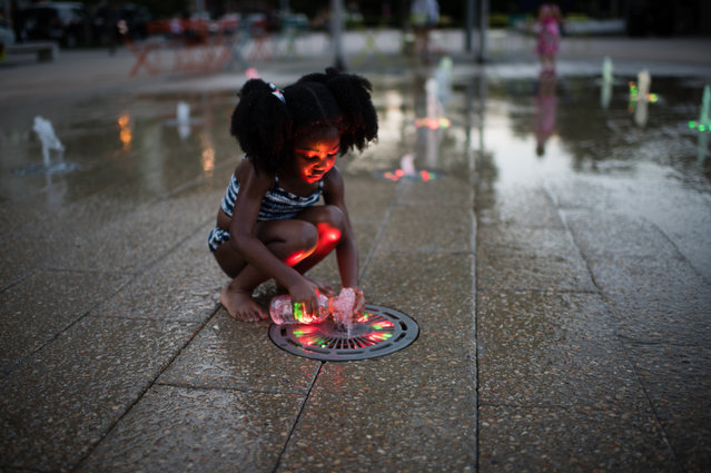 Meaghan Wallace, 3, of DC, fills a water bottle at the Canal Park sprayground on July 9, 2016. The sprayground at Canal Park is an interactive water fountain with programmable water jets embedded below the pavement that are illuminated in many colors. The park at 200 M St. SE was built on the site of the historic Washington Canal in the heart of DC's Captiol Riverfront neighborhood. It (Photo by Sarah L. Voisin/The Washington Post)