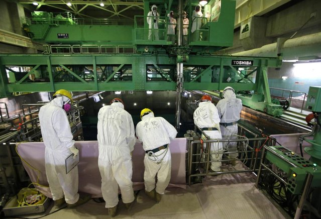 Workers wearing protective suits and masks stand next to the spent fuel pool inside the Common Pool Building, where all the nuclear fuel rods will be stored for decommissioning, at Tokyo Electric Power Co. 's tsunami-crippled Fukushima Dai-ichi nuclear power plant in Okuma, Fukushima prefecture Wednesday, March 6, 2013, ahead of the second anniversary of the March 11, 2011 tsunami and earthquake. (Photo by Issei Kato/AP Photo/Pool)