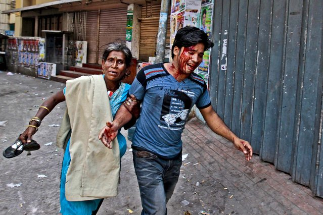A woman rushes an injured protestor to a safer location after activists clashed with police in Dhaka, Bangladesh, on March 6, 2013.The BNP activists were enrage after police fired protesters during a series of nationwide general strikes this week. (Photo by A.M. Ahad/Associated Press)