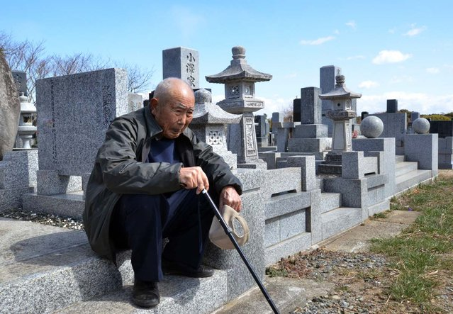 An elderly man sits as he and with his wife (not pictured) visit a cemetery to pay respects to their son who was killed in the March 2011 tsunami, in Minamisoma in Fukushima prefecture on March 11, 2013. March 11, 2013 marks the second anniversary of the 9.0 magnitude earthquake that sent a huge wall of water into the coast of the Tohoku region, splintering whole communities, ruining swathes of prime farmland and killing nearly 19,000 people. (Photo by Yoshikazu Tsuno/AFP Photo)