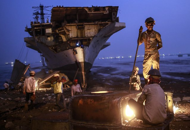 A worker uses metal cutter as others carry to dismantled parts of decommissioned Indian Navy Ship INS Vikrant at a ship breaking yard in Mumbai November 24, 2014. (Photo by Danish Siddiqui/Reuters)