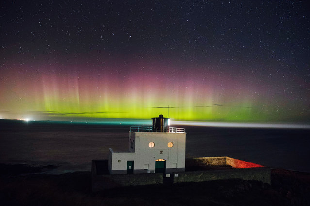 The northern lights, or aurora borealis, appear in the sky over the Bamburgh lighthouse at Stag Rock in Northumberland, England on September 28, 2016. (Photo by Owen Humphreys/PA Wire via ZUMA Press)