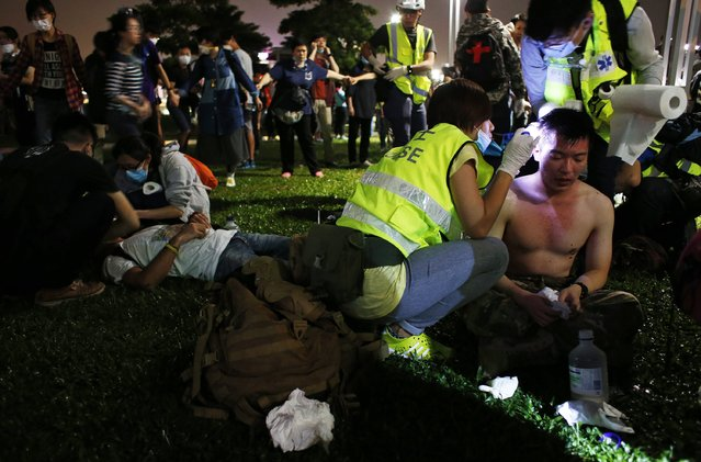 Pro-democracy protesters are treated after policemen used pepper spray during a rally close to the chief executive office in Hong Kong, November 30, 2014. (Photo by Bobby Yip/Reuters)