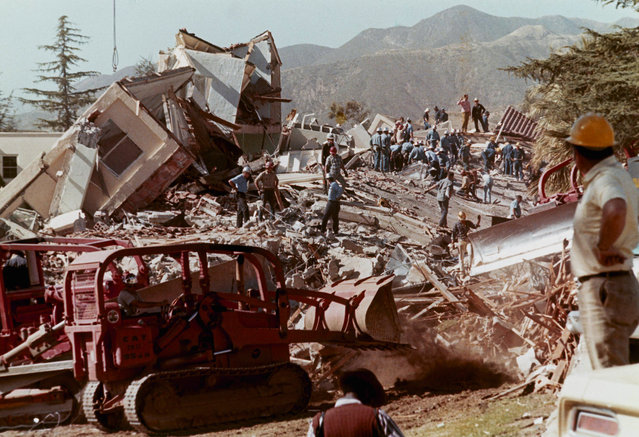 Workmen clear debris and rubble from collapsed buildings at the Veteran's Hospital in Sylmar, Calif., after a massive earthquake hit the area, February 9, 1971. (Photo by AP Photo)