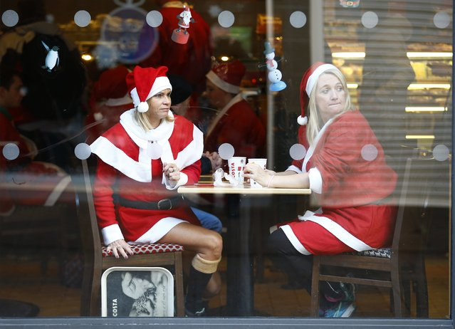 Competitors dressed in Santa costumes look from a coffee shop before an annual charity Santa fun run in Loughborough, central England, December 7, 2014. (Photo by Darren Staples/Reuters)
