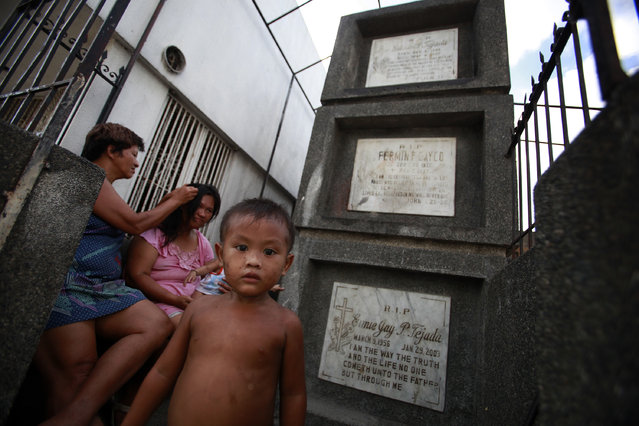 A family rests in front of tombs inside a slum in the Municipal Cemetery of Navotas, north of Manila, May 12, 2010. (Photo by Nicky Loh/Reuters)