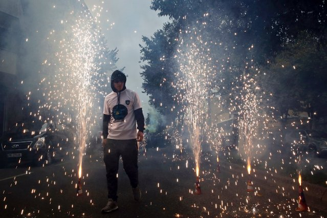 """A member of """"Dardanet"""" a Kosovo fan club, walks through fireworks to celebrate the group's arrival before the World Cup Group I qualifying soccer match between Croatia and Kosovo in Shkoder, Albania, October 6, 2016. (Photo by Visar Kryeziu/AP Photo)"""