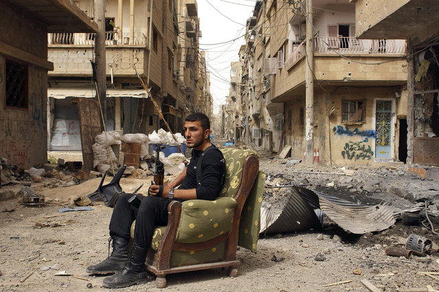 A member of the Free Syrian Army sits on a sofa in the middle of a debris-strewn street in Deir al-Zor, Syria, on April 2, 2013. (Photo by Khalil Ashawi/Reuters /The Atlantic)
