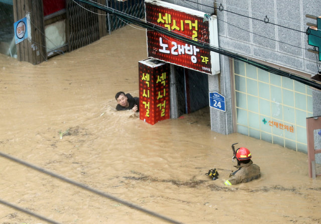 A firefighter tries to rescue a resident submerged in flood waters caused by typhoon Chaba in Ulsan, South Korea, October 5, 2016. (Photo by Kim Yong-tae/Reuters/Yonhap)