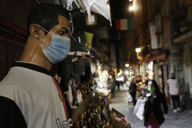 A statue of soccer star Cristiano Ronaldo, wearing a face mask, is displayed at a nativity scenes shop in San Gregorio Armeno street in Naples, Italy, Friday, November 13, 2020. The regions of Campania and Tuscany were designated red zone on Friday, signaling the dire condition of a hospitals struggling with a surge of new admissions. (Photo by Gregorio Borgia/AP Photo)