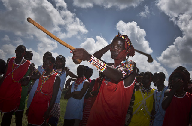 A Maasai warrior holds up his stick to line his sight, left, as he prepares to throw a Rungu, a type of wooden throwing club also known as a knobkerry, right, in a throwing competition at the annual Maasai Olympics in the Sidai Oleng Wildlife Sanctuary near to Mt Kilimanjaro, in southern Kenya Saturday, December 13, 2014. (Photo by Ben Curtis/AP Photo)