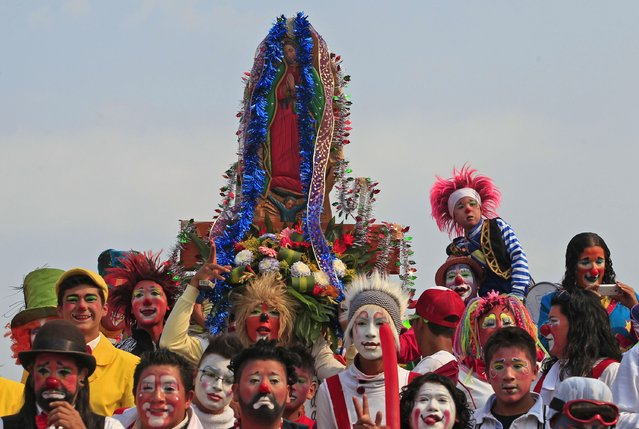 Clowns pose for a group photo holding a figurine of the Virgin of Guadalupe, during their annual pilgrimage to the Basilica of Our Lady Guadalupe to pay homage to the Virgin of Guadalupe in Mexico City December 16, 2014. (Photo by Carlos Jasso/Reuters)