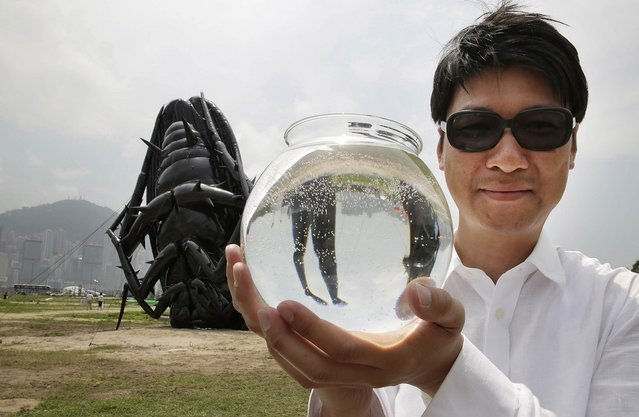 "Korean contemporary artist Tam Wai Ping poses with his inflatable sculpture, named 'Falling into the Mundane World 2013', holding a fish bowl which is a part of the piece, during the ""Inflation!"" exhibition curated by Mobile M + on April 24, 2013 in Hong Kong. The inflatable artwork is one of six on display as part of the exhibition which is open from April 25, 2013 until June 9, 2013. (Photo by Jessica Hromas)"