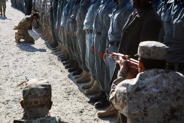 Afghan National police officers demonstrate their training during a visit by U.S. Brigadier General Christopher Bentley to an Afghan National police installation in the Nangarhar province of Afghanistan December 16, 2014. (Photo by Lucas Jackson/Reuters)