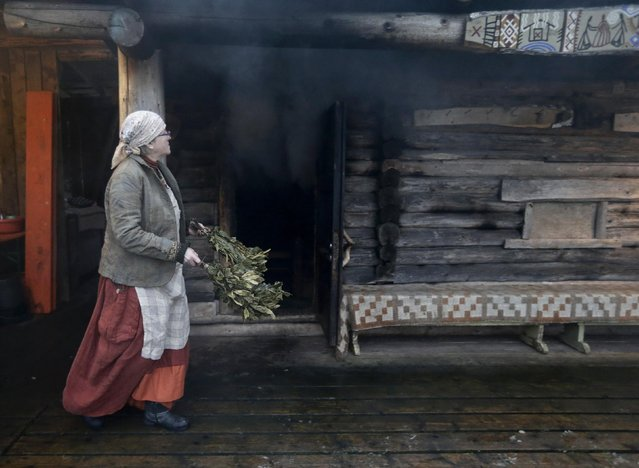 Smoke rises from the sauna as Eda Veeroja walks past with birch twigs at Mooska farm near the village of Haanja December 20, 2014. Smoke saunas are usually built without chimney and have a stove that rest on boulders where firewood is burnt until the room heats up. When the smoke is gone and the room reaches the right temperature, people sit inside and whisk each other with birch twigs. (Photo by Ints Kalnins/Reuters)