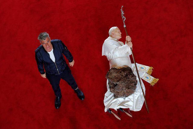 "Italian artist Maurizio Cattelan poses with his creation ""La Nona Ora"" (The Ninth Hour, 1999) prior to the opening of the exhibition ""Not Afraid of Love"" at the Hotel de la Monnaie in Paris, France, October 17, 2016. (Photo by Philippe Wojazer/Reuters)"