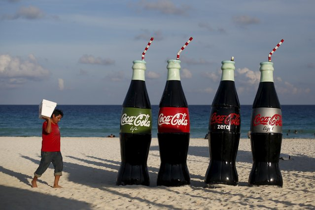 A man carries a cooler as he passes giant bottles of Coca Cola on a beach in Cancun, October 13, 2015. (Photo by Edgard Garrido/Reuters)