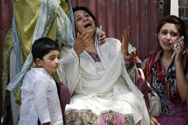 People cry as rescue workers try to save people trapped inside a burning building in central Lahore May 9, 2013. (Photo by Damir Sagolj/Reuters)