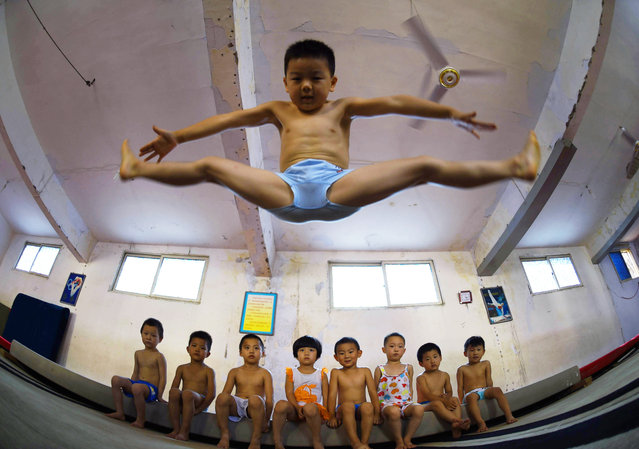 A young boy performing a straddle jump. (Photo by ChinaFotoPress/ChinaFotoPress via Getty Images)