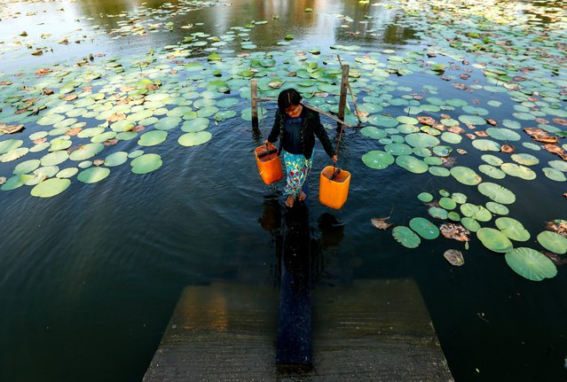 "A Young girl loads a pair of water buckets on her shoulder as she collects fresh water from a pond at Dala township that has no underground fresh water and with the township water supply system very limited, residents mostly rely on earthen rainwater ponds, the outskirt of Yangon, Myanmar, 20 March 2018. World Water Day is held annually on 22 March as a means of focusing attention on the importance of freshwater and advocating for the sustainable management of freshwater resources. The theme for World Water Day 2018 is ""Nature for Water"", exploring nature-based solutions to the water challenges we face in the 21st century. (Photo by Lynn Bo Bo/EPA/EFE/Rex Features/Shutterstock)"