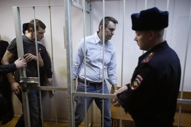 Russian opposition activist and anti-corruption crusader Alexei Navalny, 38, second right, and his brother Oleg Navalny, left, enter into the cage at a court in Moscow, Russia, Tuesday, December 30, 2014. Alexei Navalny, the anti-corruption campaigner who is a leading foe of Russian President Vladimir Putin, has been found guilty of fraud and given a suspended sentence of three and a half years. (Photo by Pavel Golovkin/AP Photo)