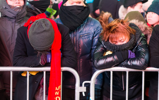 Peopls wait eagerly as revelers celebrate New Year's Eve in Times Square on December 31, 2014 in New York City. An estimated one million people from around the world are expected to pack Times Square to ring in 2015. (Photo by Andrew Theodorakis/Getty Images)