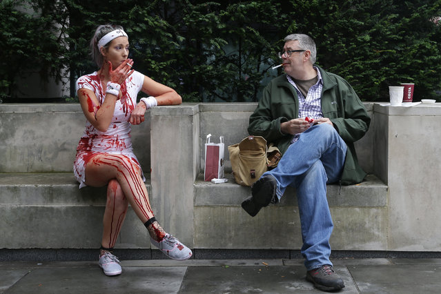 "A woman (L) sits and smokes a cigarette before participating in a ""Zombie Walk"" on World Zombie Day, in central London on October 8, 2016 World Zombie Day is an international annual event that grew from Pittsburgh' s first ever Zombie Walk at Monroeville Mall in 2006 – the setting for Dawn of the Dead. Now, more than 50 cities participate in the event, which in London, is used as an opportunity to raise money for chairty. (Photo by Daniel Leal- Olivas/AFP Photo)"