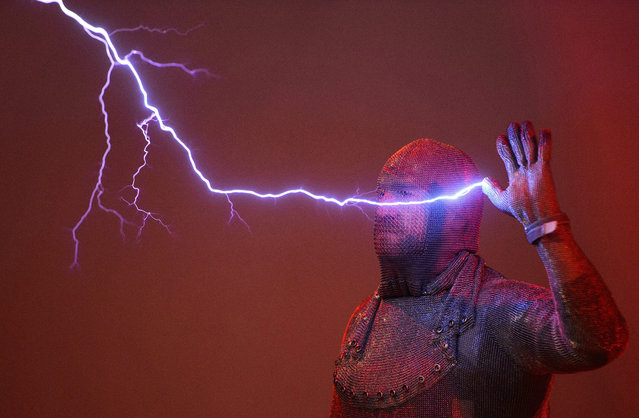 Conrad Keuck of the company Effektschmiede is struck by lightning which was produced by a Tesla coil at the Phaeno Science Center in Wolfsburg, Germany, 20 November 2015. The coat of chain mail blocks the electric current like a Faraday cage. The Phaeno celebrates its 10th anniversary. (Photo by Julian Stratenschulte/EPA)