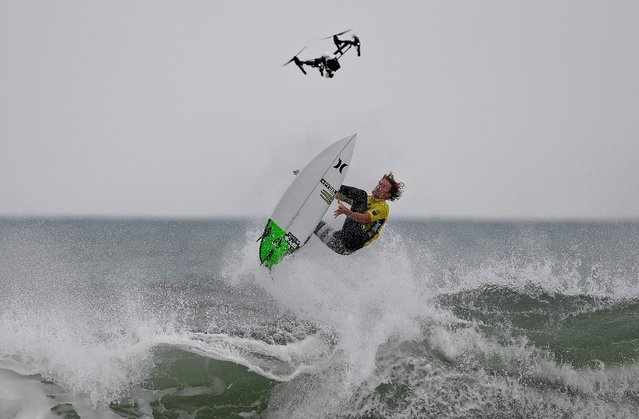 A drone flies above World Surf League World Title winner Hawaian surfer John John Florence during the final heat of the Portuguese stage of the World Surf League championship at Supertubos beach near Peniche, central Portugal, on October 25, 2016. (Photo by Francisco Leong/AFP Photo)