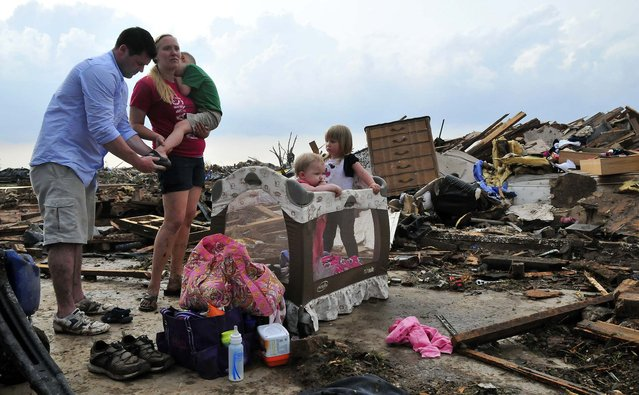 Kelcy Trowbridge with her brother-in-law Dustin Weher and her three children, from left, Colby, Karley and Kynlee Trowbridge, in front of Kelcy's destroyed house, near Moore, Okla., May 20, 2013. (Photo by Nick Oxford/The New York Times)