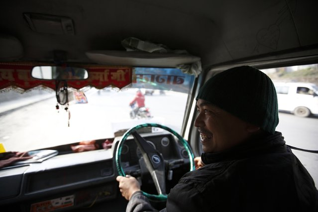 Janak Shrestha, the driver of a women-only bus, smiles as he speaks with a passenger (unseen) in Kathmandu January 6, 2015. (Photo by Navesh Chitrakar/Reuters)