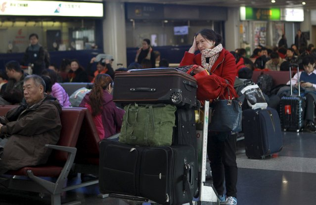 Stranded passengers wait next to their luggages at the Beijing Capital International Airport, after heavy snowfall hits Beijing, China, November 23, 2015. Snowstorms have swept across a vast area of north China, disrupting traffic, grounding flights and slowing bullet trains in Beijing, Tianjin, Hebei Province and the Inner Mongolia Autonomous Region, while nearly 300 flights were cancelled at Beijing Capital International Airport, Xinhua News Agency reported. (Photo by Reuters/China Daily)