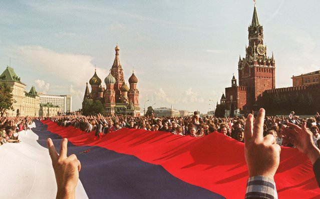 """People holding a huge Russian flag flash victory signs on August 22, 1991 on Red Square in Moscow as they celebrate the failure of a hardline communist- led coup which nearly toppled Soviet President Mikhail Gorbachev. The coup was headed 19 August by the members of the self- styled """"committee for the state of emergency"""" or the """"gang of eight"""", including Soviet Vice President Gennady Yanayev and KGB chief Vladimir Kryuchkov. The same day, thousands in Moscow, Leningrad and other cities answered Russian Republic President Boris Yeltsin' s call to raise barricades against tanks and troops. (Photo by Anatoly Sapronenkov/AFP Photo)"""