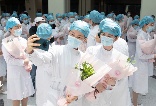 Chinese nurses take a selfie with a mobile phone during a ceremony celebrating International Nurses Day at Tongji Hospital in Wuhan, Hubei province, China, 12 May 2020. International Nurses Day is marked on 12 May, the anniversary of Florence Nightingale's birth, as health workers around the world face unprecedented risks combating the Covid-19 coronavirus outbreak. (Photo by EPA/EFE/China Stringer Network)