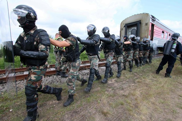 Lithuanian special forces take part in an exercice focused on securing the European Union' s external border ahead of the World Cup football matches to be held in Kaliningrad enclave on May 23, 2018 at railway station of the Lithuanian village of Kena, a border crossing point with Belarus. Thousands of Russian football fans are expected to cross the Baltic state to reach World Cup matches in the neighbouring Russian exclave of Kaliningrad. Sandwiched between Poland, Lithuania and the Baltic Sea, Kaliningrad will host four matches next month, starting with a game between Croatia and Nigeria on June 16. Lithuanian special forces simulate the detention of aggressive football fans. (Photo by Petras Malukas/AFP Photo)