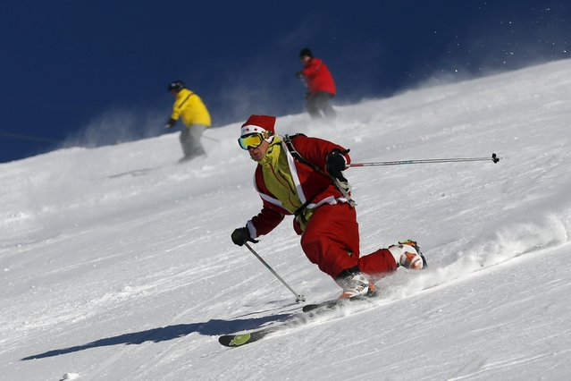 A man, dressed as Santa Claus, takes a curve with his telemark during a promotional event on the opening weekend in the alpine ski resort of Verbier, Switzerland, December 6, 2015. Skiers dressed as Santa Claus were granted free access to the resort on the day of Saint-Nicolas. (Photo by Denis Balibouse/Reuters)