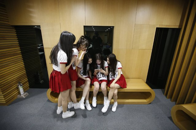 Members of South Korean girl group GFriend watch a recording of their stage performance during a dress rehearsal for The Show in Seoul January 20, 2015. (Photo by Kim Hong-Ji/Reuters)