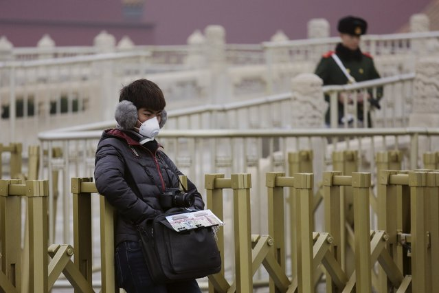 "A man offering photo services wears a mask protecting from extreme smog at the Tiananmen Gate in Beijing December 8, 2015 as China's capital issues its first ever ""red alert"" for pollution. (Photo by Damir Sagolj/Reuters)"