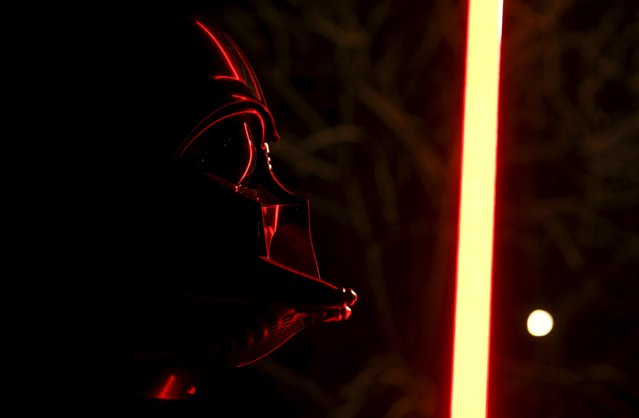 Darth Mykolaiovych Vader, who is dressed as the 'Star Wars' character Darth Vader, poses for a picture as he shows exercises with a lightsaber at a park in Odessa, Ukraine, December 3, 2015. (Photo by Valentyn Ogirenko/Reuters)