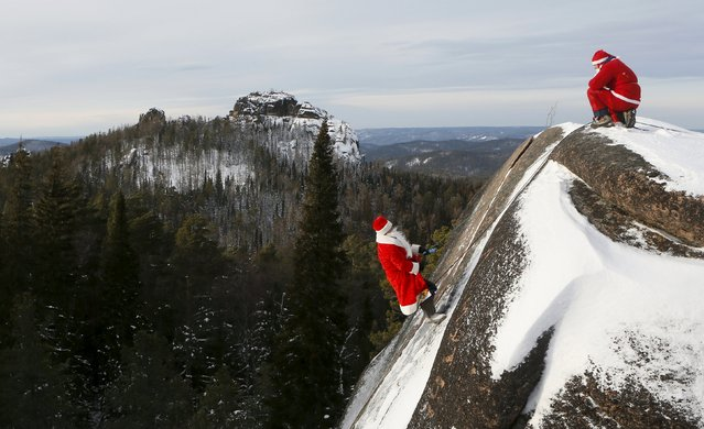 "A member of the ""Sibspas"" Siberian search and rescue group dressed as Santa Claus (R), waits for his team mate, dressed as Father Frost, the Russian equivalent of Santa Claus, as he climbs the rock named ""The Fourth Stolb"" (the Fourth Pillar) at the Stolby national nature reserve during a training session of the Russian Emergencies Ministry, outside the Siberian city of Krasnoyarsk, Russia December 15, 2015. (Photo by Ilya Naymushin/Reuters)"