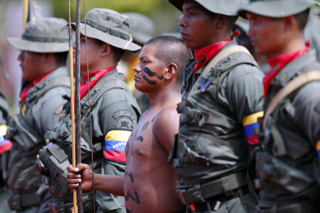 "A Venezuelan indian (C) from the Amazon tribes belonging to the ""Platoon of silent weapons"" stands at attention with his fellow soldiers from the Venezuelan army during a welcome ceremony for Colombian President Juan Manuel Santos (not in picture) in Puerto Ayacucho July 22, 2013. (Photo by Jorge Silva/Reuters)"