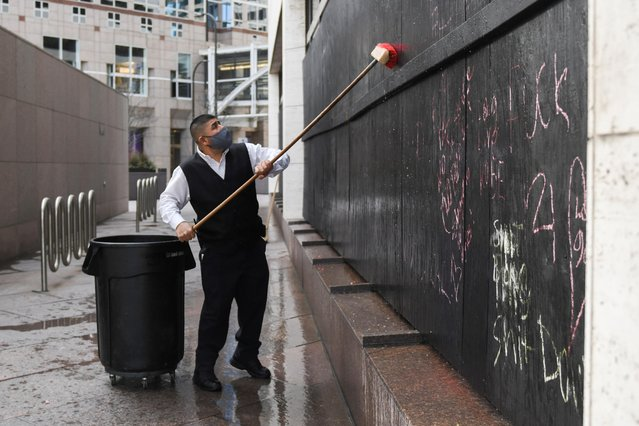 A worker washes away chalked messages of protest from the boarded up facade of the US Bank Plaza tower, across the street from the Hennepin County Government Center in downtown Minneapolis during the first day of jury selection for the trial of Derek Chauvin, the former Minneapolis policeman accused of killing George Floyd, in Minneapolis, Minnesota, U.S. March 8, 2021. (Photo by Nicholas Pfosi/Reuters)