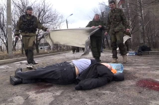 In this screen shot made available by RU-RTR, pro-Russia rebels cover a body of a victim outside clinic 27, damaged after shelling, in Donetsk, Ukraine, Wednesday, February 4, 2015. Heavy shelling in the rebel stronghold of Donetsk in eastern Ukraine on Wednesday afternoon killed at least five people and damaged a hospital, six schools and five kindergartens, local officials said. (Photo by AP Photo/RU-RTR)