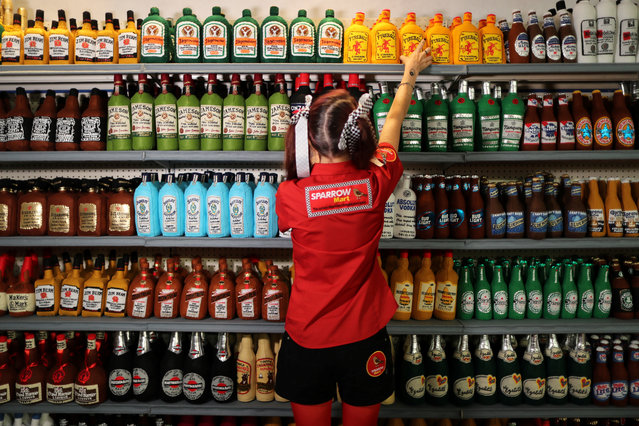 British artist Lucy Sparrow, 32, adjusts bottles of alcohol on shelves in her art installation supermarket in which everything is made of felt, in Los Angeles, California on July 31, 2018. (Photo by Lucy Nicholson/Reuters)